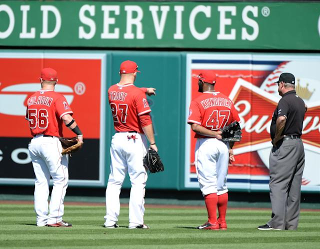 ANAHEIM, CA - SEPTEMBER 22: Kole Calhoun #56, Mike Trout #27 and Howie Kendrick #47 of the Los Angeles Angels point out bees in the outfield to the umpire which delayed the game earlier in the third inning during the fourth inning at Angel Stadium of Anaheim on September 22, 2013 in Anaheim, California. (Photo by Harry How/Getty Images)