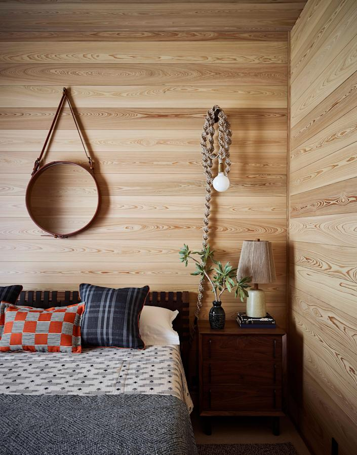 A porthole-like mirror by Jacques Adnet and knotted Helix sconce by Windy Chien in the guest bedroom underscore the home's nautical influence—as do the top-to-bottom cypress planks, as you would see in a ship's cabin. Bedding by Clarence House, Zak & Fox, Jennifer Shorto, and Clay McLaurin Studio adds dash (a pattern mashup) without flash (a reserved color palette).