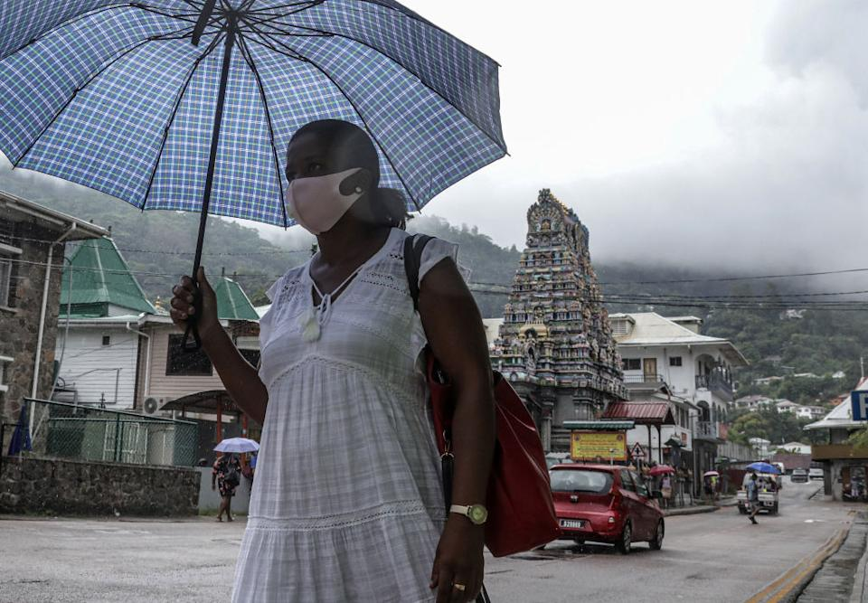A woman holding an umbrella walks in a street in capital Victoria.