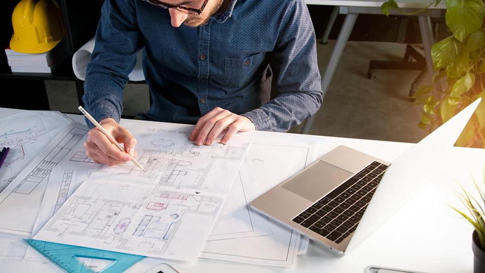 Architect working in office with house project on desk.