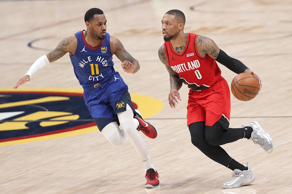 DENVER, COLORADO - MAY 22: Damian Lillard #0 of the Portland Trail Blazers brings the ball down the court against Monte Morris #11 of the Denver Nuggets in the fourth quarter during Game One of their Western Conference first-round playoff series at Ball Arena on May 22, 2021 in Denver, Colorado. NOTE TO USER: User expressly acknowledges and agrees that, by downloading and or using this photograph, User is consenting to the terms and conditions of the Getty Images License Agreement. (Photo by Matthew Stockman/Getty Images)