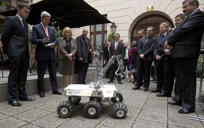"U.S. Secretary of State John Kerry, 2nd left, controls a Mars rover prototype named ""Hyperion"" made by Polish University students, right, who won first place in the Mars Society's annual international rover challenge, in Warsaw Tuesday Nov. 5, 2013. (AP Photo/Jason Reed, Pool)"