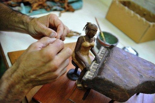 Cuban tobacco sculptor Janio Nunez works on his piano player sculpture made out of tobacco leaves at his workshop in Guanabo. The Cuban sculptor uses the same sticky leaves and time-honored rolling techniques that go into the famed cigars enjoyed by his subjects, and which was celebrated at last week's 14th annual Havana Festival