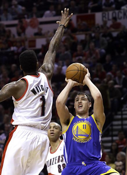 Golden State Warriors guard Klay Thompson, right, shoots against Portland Trail Blazers forward Dorell Wright during the first half of an NBA basketball game in Portland, Ore., Sunday, March 16, 2014. (AP Photo/Don Ryan)