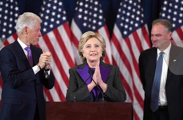 Hillary Clinton makes a concession speech standing at a podium in front of American flags next to former President Bill Clinton and Sen. Tim Kaine