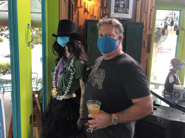 Brack May poses with a masked mannequin in his New Orleans restaurant, Cowbell, on Friday, Aug. 6, 2021. May's eatery is among the first in New Orleans to require proof of vaccination against COVID-19 for indoor diners. He said some have been angered by the requirement but others welcome it. (AP Photo/Kevin McGill)