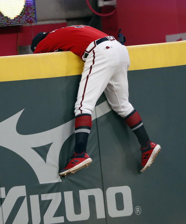 Atlanta Braves left fielder Ronald Acuna Jr. reaches over the wall but cannot get to a ball hit for a home run by Colorado Rockies' Trevor Story in the fourth inning of a baseball game Friday, April 26, 2019, in Atlanta. (AP Photo/John Bazemore)
