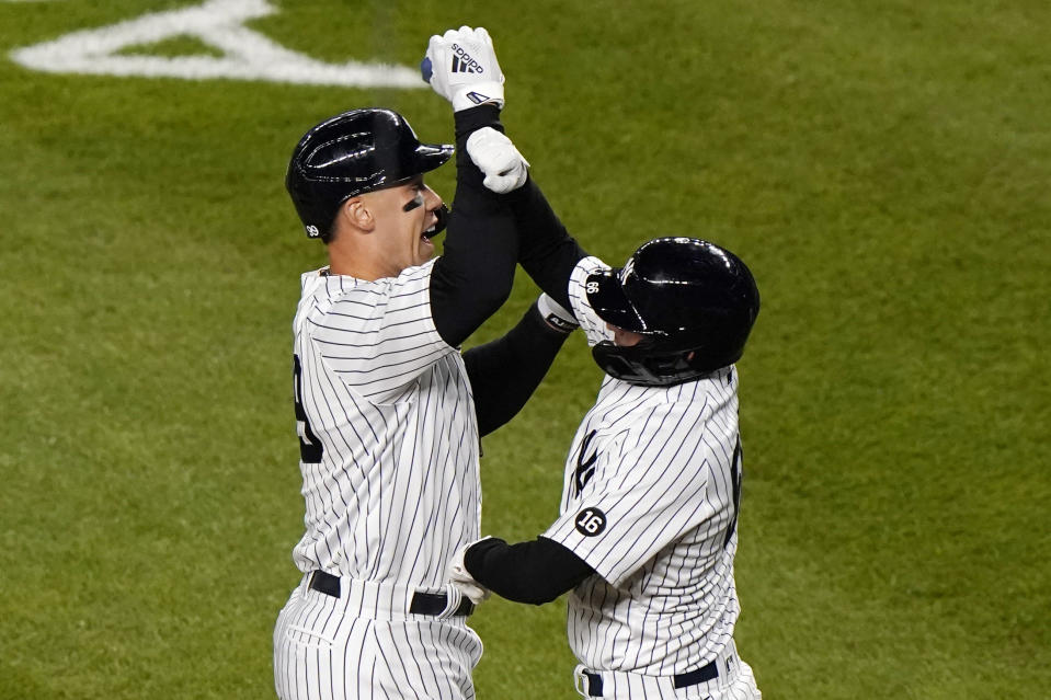 New York Yankees Aaron Judge, left, celebrates with Yankees Kyle Higashioka after Higashioka scored on Judge's eight-inning, three-run home run in a baseball game against the Baltimore Orioles, Tuesday, April 6, 2021, at Yankee Stadium in New York. (AP Photo/Kathy Willens)