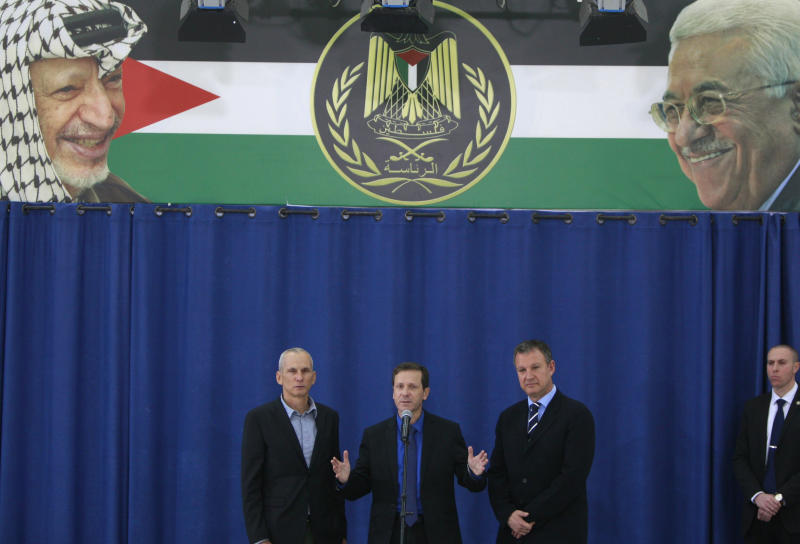 CAPTION ADDITION--ADDS NAMES OF PEOPLE IN BACKGROUND POSTER -- Israeli new labor party leader Isaac Herzog speaks during a press conference flanked by his party officials Erel Margalit, right, and Omer Bar-Lev after their meeting with Palestinian President Mahmoud Abbas in the West Bank city of Ramallah, Sunday, Dec. 1, 2013. Poster in background shows late Palestinian leader Yasser Arafat and President Mahmoud Abbas. (AP Photo/Majdi Mohammed)