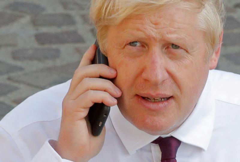 Britain's Prime Minister Boris Johnson makes a phone call as he walks near the summit venue during the G7 summit in Biarritz, France, August 25, 2019. REUTERS/Philippe Wojazer