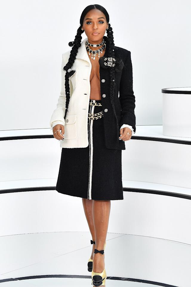 in a black and white Chanel tweed jacket with a matching black skirt with white trimming, accessorized with large Chanel brooch at the Chanel show in Paris.
