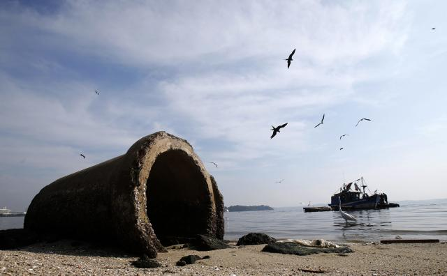 A pipe is seen near a fishing boat on Fundao beach in the Guanabara Bay in Rio de Janeiro