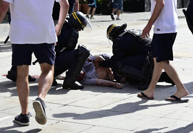 (FILES) This file photo taken on June 11, 2016 shows policemen attending to England fan Andrew Bache following clashes between fans of England and Russia in the city of Marseille, southern France, ahead of the Euro 2016 football match between England and Russia.A Russian football hooligan sought by authorities for savagely attacking a British fan at Euro 2016 in France has been arrested, German police said on February 22, 2018 (AFP Photo/TOBIAS SCHWARZ )