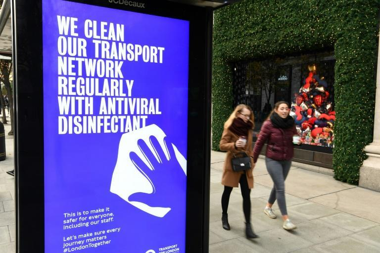 Pedestrians walk past a sign about how the public areas of the transport network are disinfected regularly as a hygiene precaution during the novel coronavirus pandemic on Oxford Street in London