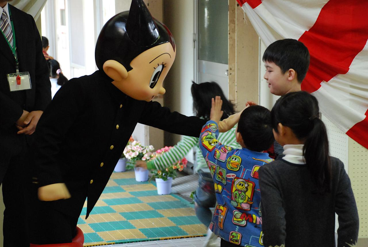 TOKYO - APRIL 06:  In this handout image provided by the Board of Education, Shinjuku City, Japanese famous cartoon character Tetsuwan Atom or Astro Boy (L) pats a child's head after the entrance ceremony of Totsuka Daisan Elementary School on April 6, 2010 in Tokyo, Japan. In the original work by cartoon artist Osamu Tezuka, Astro Boy was set to be born on April 7, 2003 and would turn 7 years old, when children enter elementary schools in Japan in 2010.  (Photo by Shinjuku City Board Of Education via Getty Images)