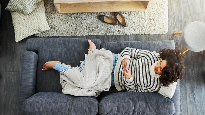 High angle shot of an attractive young woman using her cellphone while relaxing on a couch at home.