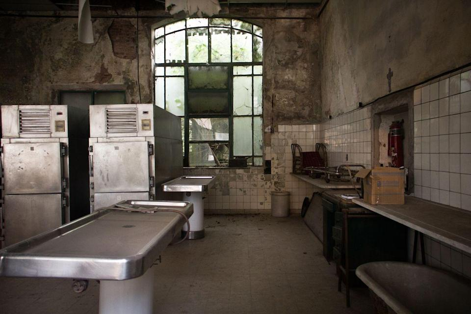 <p>A giant window, fit with cracked and shattered panes, overlooks this former autopsy room.</p>