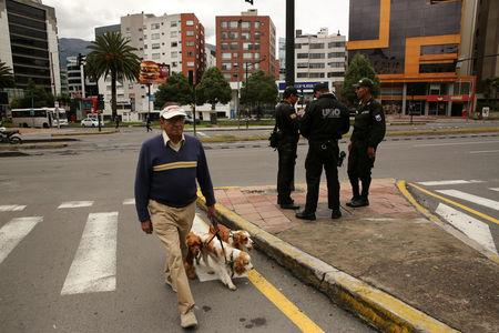 A man walks his dogs near  police in front of the Electoral National Council  (CNE) headquarters prior to Sunday presidential election in Quito, Ecuador, April 1, 2017. REUTERS/Mariana Bazo