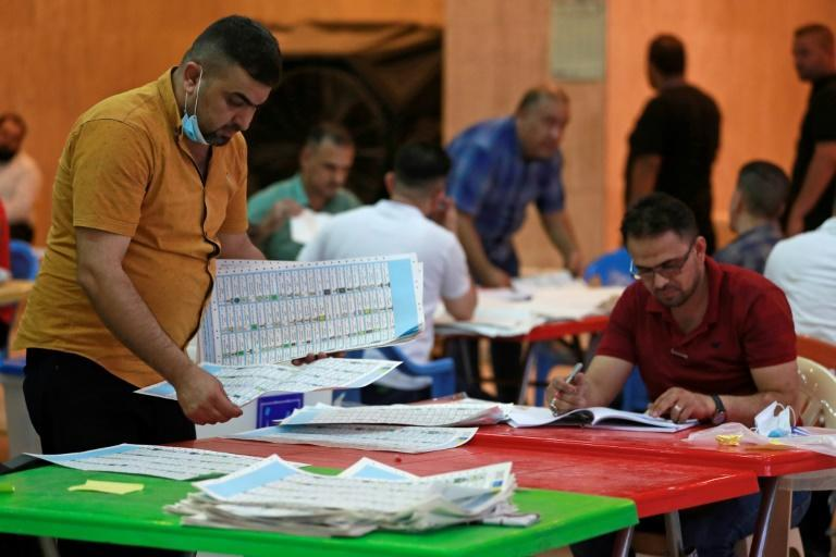 Employees of Iraq's Independent High Electoral Commission conduct a manual count of votes following the parliamentary elections in Baghdad's Green Zone area on October 13, 2021 (AFP/AHMAD AL-RUBAYE)
