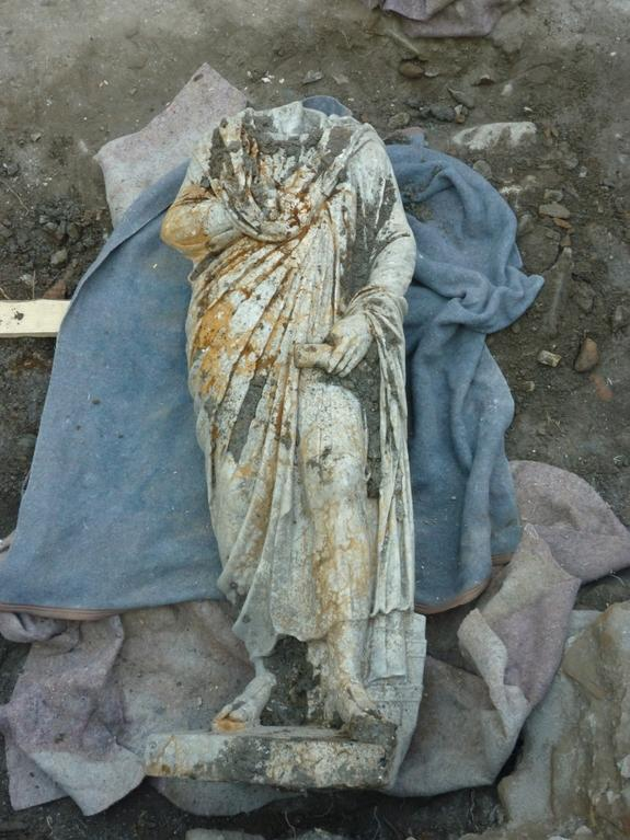 Statue A is dressed in a civilian costume of a cloak and tunic.