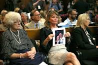 """An attendee holds a photo of Cheri Domingo and her boyfriend Gregory Sanchez, killed in 1981, during the arraignment of Joseph James DeAngelo, the suspected """"Golden State Killer"""" on April 27, 2018 in Sacramento"""