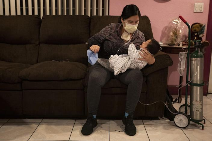 A woman in a mask sits on a couch with her newborn son, with an oxygen tank by her side
