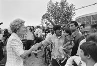 """Then-first lady Pat Nixon reaches from San Diego across the border - then marked by a barbed wire fence - to greet people on the Tijuana, Mexico side during the dedication of Friendship Park on Aug. 18, 1971. In the days before Joe Biden became president, construction crews worked quickly to finish Donald Trump's wall at an iconic cross-border park overlooking the Pacific Ocean that then-first lady Pat Nixon inaugurated in 1971 as symbol of international friendship. Biden on Wednesday, Jan. 20, 2021 ordered a """"pause"""" on all wall construction within a week, one of 17 executive edicts issued on his first day in office, including six dealing with immigration. (Richard Nixon Presidential Library and Museum via AP)"""