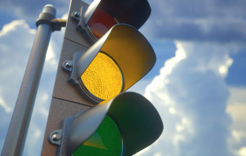 Traffic light with yellow light on, signal for proceed with caution.