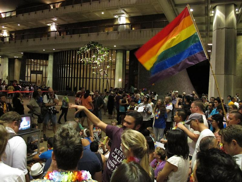 Proponents of gay marriage rally outside House chambers at the Hawaii Capitol in Honolulu on Friday, Nov. 8, 2013. The House debate played out into the night amid noisy crowds outside the chamber and maneuvering inside from lawmakers for and against the bill. (AP Photo/Oskar Garcia)