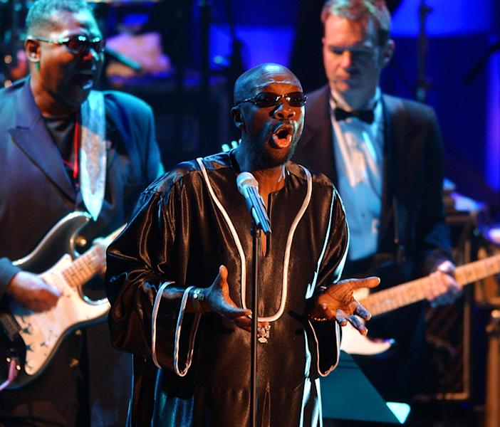 "FILE - In this March 18, 2002 file photo, singer Isaac Hayes, center, performs during the opening of the Rock and Roll Hall of Fame inductee ceremony at New York's Waldorf Astoria. Hayes was among the 2002 class of inductees into the hall of fame. Hal David, the stylish, heartfelt lyricist who teamed with Burt Bacharach on dozens of timeless songs for movies, television and a variety of recording artists in the 1960s and beyond, died Saturday, Sept. 1, 2012. He was 91. David wrote the lyrics for a song Hayes performed with Dionne Warwick entitled ""Walk On By."" (AP Photo/Kathy Willens, File)"