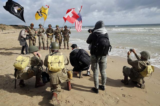 <p>Men dressed with U.S. 101st Airborne Division uniforms pose on the beach during commemorations marking the 73th anniversary of D-Day, the June 6, 1944, landings of Allied forces in Normandy. (Photo: Chesnot/Getty Images) </p>