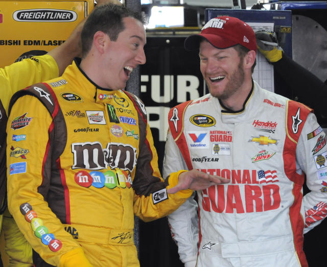 Kyle Busch, left, talks with Dale Earnhardt Jr, right, before practice for Sunday's NASCAR Sprint Cup series Coca-Cola 600 auto race at Charlotte Motor Speedway in Concord, N.C., Thursday, May 22, 2014. (AP Photo/Mike McCarn)