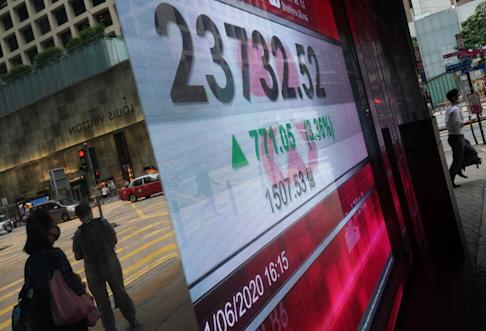 People seen in the reflection, as an electronic board shows the closing Hang Seng Index number in Central on 1 June 2020. Photo: Felix Wong