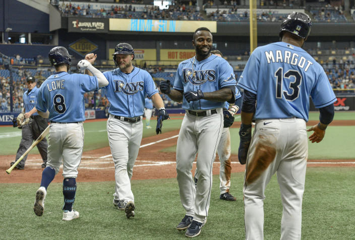 Tampa Bay Rays designated hitter Randy Arozarena, second right, celebrates a grand slam off Baltimore Orioles reliever Cesar Valdez with Brandon Lowe (8), Austin Meadows and Manuel Margot (13) during the seventh inning of a baseball game Sunday, June 13, 2021, in St. Petersburg, Fla. (AP Photo/Steve Nesius)