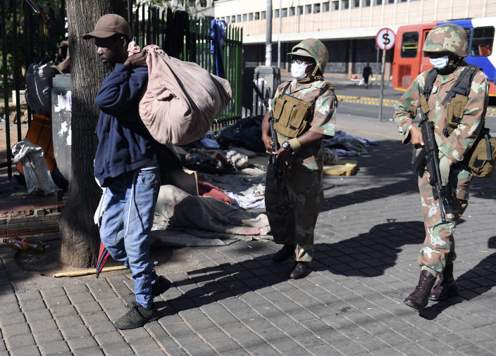 Soldiers apprehend a homeless man in a roundup of homeless people in downtown Johannesburg Friday, March 27, 2020, after South Africa went into a nationwide lockdown for 21 days in an effort to mitigate the spread to the coronavirus. The new coronavirus causes mild or moderate symptoms for most people, but for some, especially older adults and people with existing health problems, it can cause more severe illness or death(AP Photo)