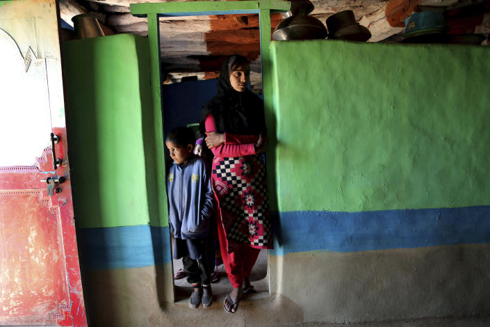 Sister of Mohammad Aslam, an Indian porter who was allegedly killed by the Pakistan army along the line of control, stands inside her home in Poonch, India, Wednesday, Dec. 16, 2020. The terrain along the Line of Control, that for the past 73 years divided the region between the two nuclear-armed rivals of India and Pakistan, is tough and the life of civilians living in the area is even tougher, with them often caught in the line of fire. Over the last year, troops from the two sides have traded fire almost daily along the frontier, leaving dozens of civilians and soldiers dead. (AP Photo/Channi Anand)