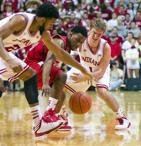 Nebraska's Benny Parker, center, battles for the ball with Indiana's Christian Watford (2) and Jordan Hulls (1) during the second half of an NCAA college basketball game, Wednesday, Feb. 13, 2013, in Bloomington, Ind. Indiana won 76-47. (AP Photo/Doug McSchooler)