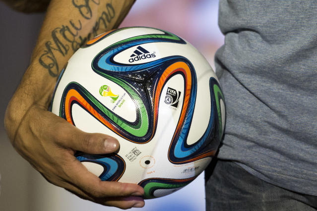 FILE - In this Dec. 3, 2013 file photo, Brazilian soccer player Hernanes holds the 2014 World Cup official soccer ball, called Brazuca, after it was unveiled in Rio de Janeiro, Brazil. The competition on the pitch in has yet to start, but the fight over World Cup consumers is already intense _ and no more so than between the athletic companies that are jockeying for their once-every-four-years shot at the ever-growing soccer market. (AP Photo/Victor R. Caivano, File)