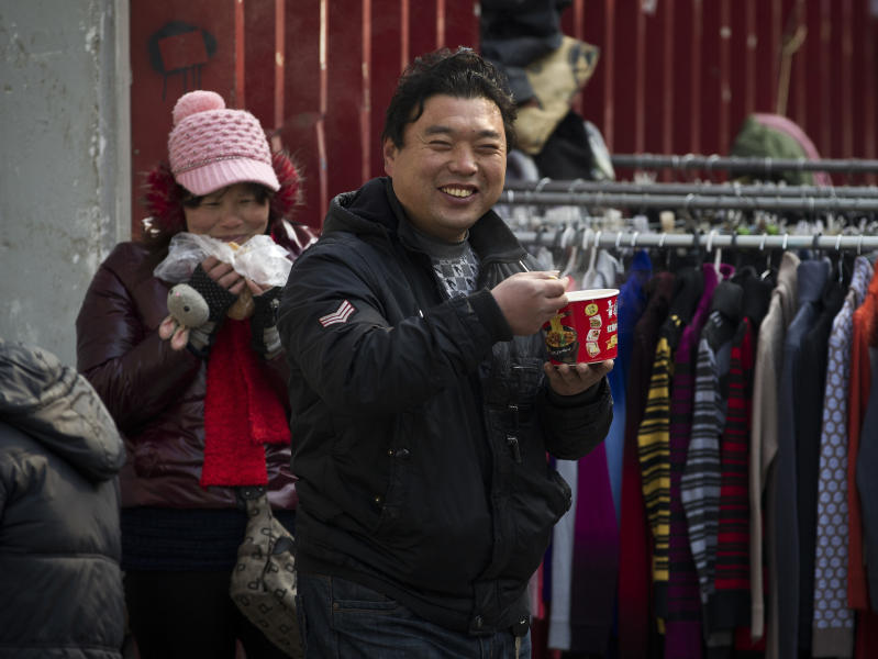 Vendors have a breakfast at a morning market in Beijing Friday, March 9, 2012. China's inflation fell sharply in February, giving Beijing more leeway to stimulate its slowing economy. Inflation in politically sensitive food costs declined even more markedly, falling to 6.2 percent from the previous month's 10.5 percent. (AP Photo/Andy Wong)