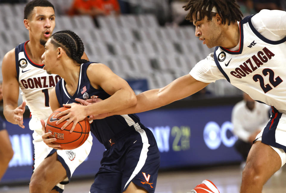 Virginia guard Kihei Clark (0) controls the ball as Gonzaga forward Anton Watson (22) reaches in and Gonzaga guard Jalen Suggs (1) looks on during the first half of an NCAA college basketball game, Saturday, Dec. 26, 2020, in Fort Worth, Texas. (AP Photo/Ron Jenkins)