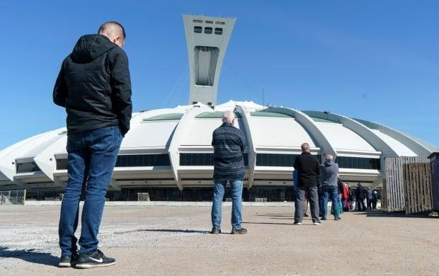 People wait in line at a COVID-19 vaccination clinic to receive the AstraZeneca vaccine at Olympic Stadium in Montreal earlier this month. Quebecers 55 and over can now get the AstraZeneca vaccine at walk-in clinics across the province.