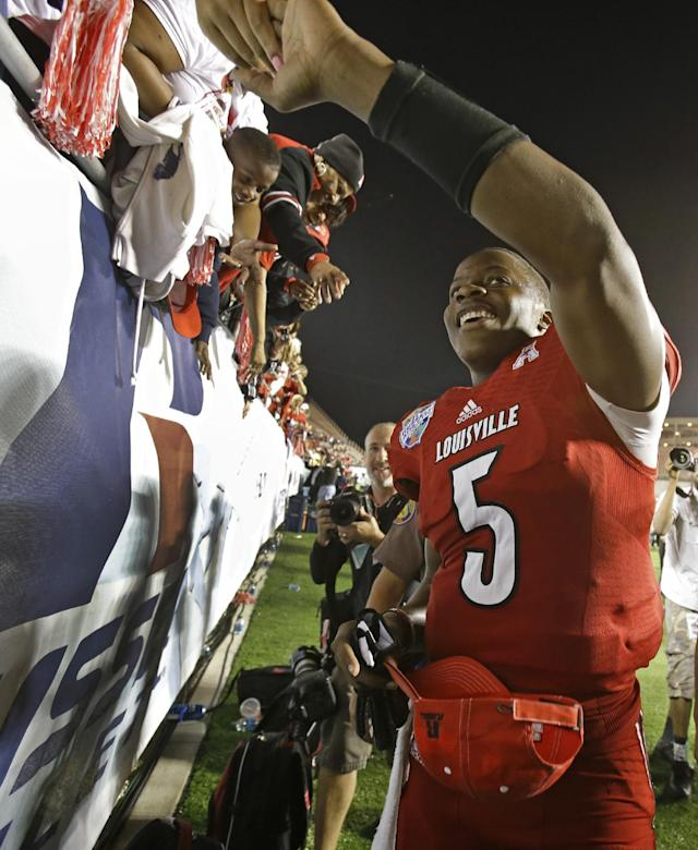 Louisville quarterback Teddy Bridgewater greets fans after Louisville defeated Miami 36-9 in the Russell Athletic Bowl NCAA college football game in Orlando, Fla., Saturday, Dec. 28, 2013. (AP Photo/John Raoux)