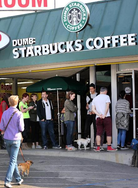 """People line up at Dumb Starbucks coffee in Los Angeles Monday, Feb. 10, 2014. The store resembles a Starbucks with a green awning and mermaid logo, but with the word """"Dumb"""" attached above the Starbucks sign. Spokeswoman Laurel Harper says the store is not affiliated with Starbucks and, despite the humor, the store cannot use the Starbucks name. (AP Photo/Damian Dovarganes)"""