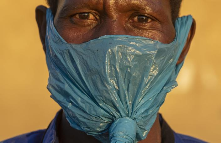 FILE — In this May 6, 2020 file photo a man wears a plastic bag for a mask on his face as a precaution against the spread of the coronavirus, in Katlehong, Johannesburg. (AP Photo/Themba Hadebe, File)