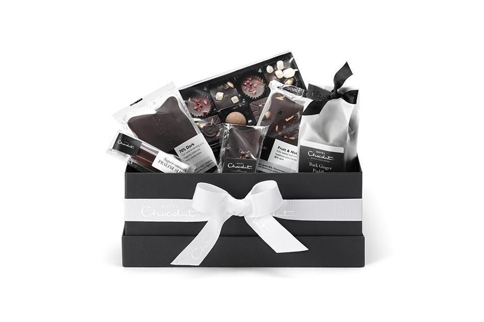 """<p>Vegan foodies, rejoice! This festive season, Hotel Chocolat is selling an All Dark Hamper Collection which boasts a fruit and nut chocolate slab, hazelnut log and ginger puddles – all wrapped up in a chic bow. <em><a href=""""https://www.hotelchocolat.com/uk/the-all-dark-collection.html#start=1?utm_source=rakuten&utm_medium=referral&utm_campaign=2116208:Skimlinks.com&utm_content=10&utm_term=UKNetwork&ranMID=43303&ranEAID=TnL5HPStwNw&ranSiteID=TnL5HPStwNw-DNkZ.ib1PgSxbRiqYYhaTQ"""" rel=""""nofollow noopener"""" target=""""_blank"""" data-ylk=""""slk:Hotel Chocolat"""" class=""""link rapid-noclick-resp"""">Hotel Chocolat</a>, £27.50</em> </p>"""
