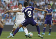 Real Madrid's James Rodriguez, left, vies for the ball with Valladolid's Pedro Porro during the Spanish La Liga soccer match between Real Madrid and Valladolid at the Santiago Bernabeu stadium in Madrid, Spain, Saturday, Aug. 24, 2019. (AP Photo/Paul White)
