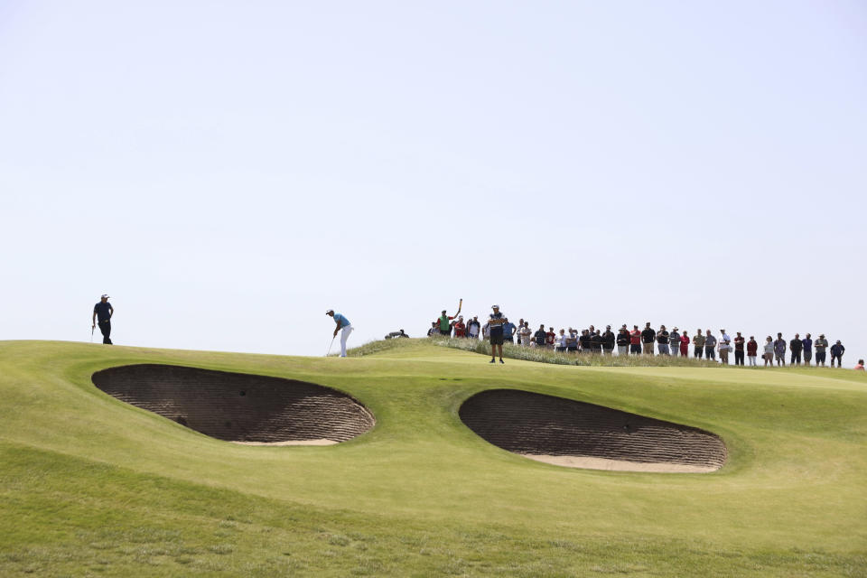 United States' Xander Schauffele, at centre, putts watched by Benjamin Hebert of France on the 10th green during the third round of the British Open Golf Championship at Royal St George's golf course Sandwich, England, Saturday, July 17, 2021. (AP Photo/Ian Walton)