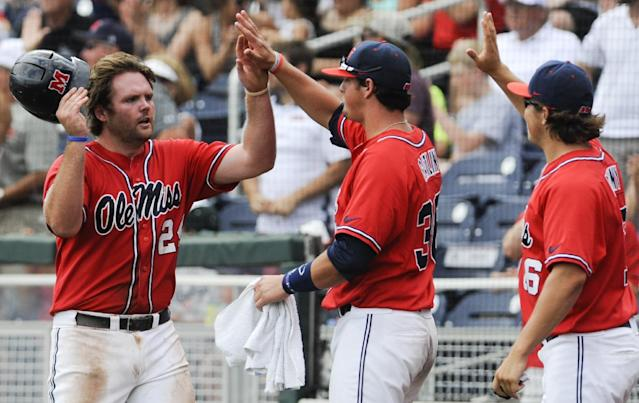 Mississippi's Sikes Orvis, left, is greeted by teammates Will Allen, center, and Matt Denny, right, after scoring against Texas Tech on a single by Holt Perdzock during the seventh inning of an elimination baseball game at the NCAA College World Series in Omaha, Neb., Tuesday, June 17, 2014. (AP Photo/Eric Francis)