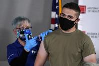 Arizona Air National Guard medic Will Smith, right, receives one of the first doses of the Pfizer-BioNTech vaccine for COVID-19 at the Arizona Department of Health Services State Laboratory from nurse Machrina Leach, Wednesday, Dec. 16, 2020, in Phoenix. The Pfizer vaccine was almost 95 percent effective at preventing patients from contracting COVID-19 and caused no major side effects in a trial of nearly 44,000 people. (AP Photo/Ross D. Franklin)