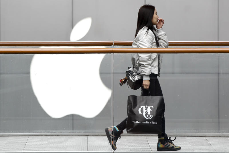 FILE - In this Feb. 26, 2019, file photo, a woman carries a paper bag containing goods purchased from American brand Abercrombie & Fitch walks past an Apple store at the capital city's popular shopping mall in Beijing. Companies who do business with China walk a fine line to stay aligned with U.S. values such as freedom of speech and democracy while avoiding offending China, where they stand to make billions of dollars. (AP Photo/Andy Wong, File)